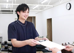 ボードをお客様に渡しているスタッフの写真